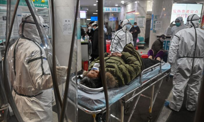 Medical staff members wearing protective clothing arrive with a patient at the Wuhan Red Cross Hospital in Wuhan, China, on Jan. 25, 2020. (Hector Retamal/AFP via Getty Images)