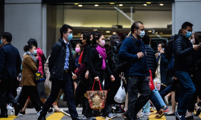 Pedestrians wear face masks as they cross a road in Hong Kong on February 3, 2020. (ANTHONY WALLACE/AFP via Getty Images)