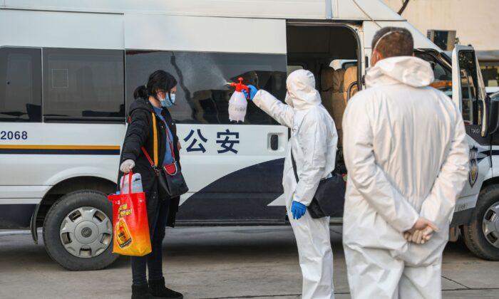 This photo taken on Feb. 3, 2020 shows a medical staff member (C) spraying disinfectant on a patient after returning from a hospital and re-entering a quarantine zone in Wuhan, the epicentre of the new coronavirus outbreak, in China's central Hubei province. (STR/AFP via Getty Images)