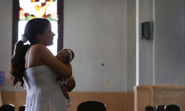 A Cuban mother holds her baby as she visits the El Cobre church in Santiago de Cuba, Cuba, on Sept. 19, 2015. (Joe Raedle/Getty Images)
