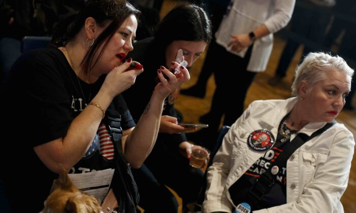 A woman with her dog applies lipstick as she attends Democratic presidential candidate former Vice President Joe Biden's Iowa caucus night event at Drake University in Des Moines, Iowa, on Feb. 3, 2020. (Joshua Lott/Getty Images)