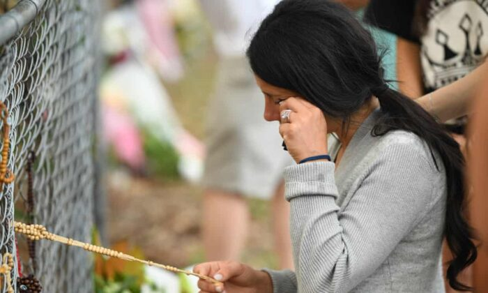 Leila Geagea pauses near flowers placed at the scene where a vehicle fatally hit three of her children in the Sydney suburb of Oatlands, on on Feb. 2, 2020. (Joel Carrett/AAP)