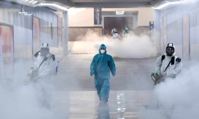 Volunteers in protective suits disinfect a railway station as the country is hit by an outbreak of the new coronavirus, in Changsha, Hunan province, China, on Feb. 4, 2020. (cnsphoto via Reuters)