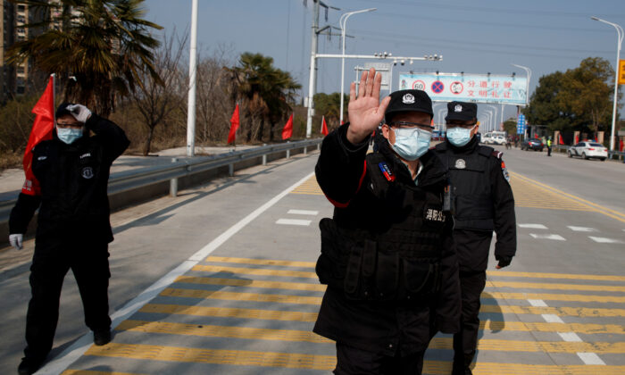 Security personnel attempt to prevent the photographer from taking pictures at a checkpoint at the Jiujiang Yangtze River Bridge as the country is hit by an outbreak of the novel coronavirus, in Jiujiang, Jiangxi Province, China, on Feb. 4, 2020. (Thomas Peter/Reuters)