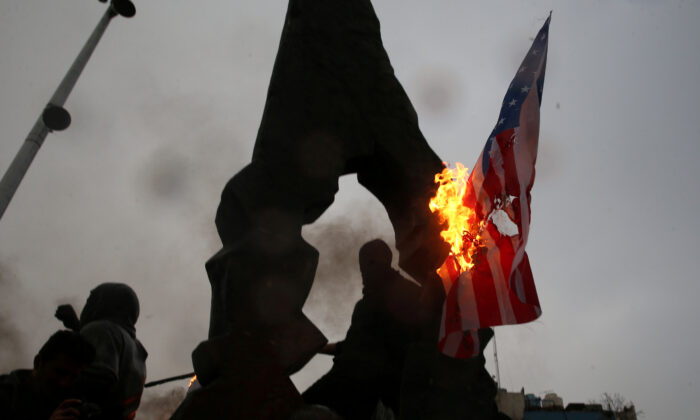 Iranians burn U.S and Israeli flags as they gather to mourn General Qassem Soleimani, head of the elite Quds Force, who was killed in an air strike at Baghdad airport, in Tehran, Iran Jan. 4, 2020. (Nazanin Tabatabaee/WANA (West Asia News Agency) via Reuters)