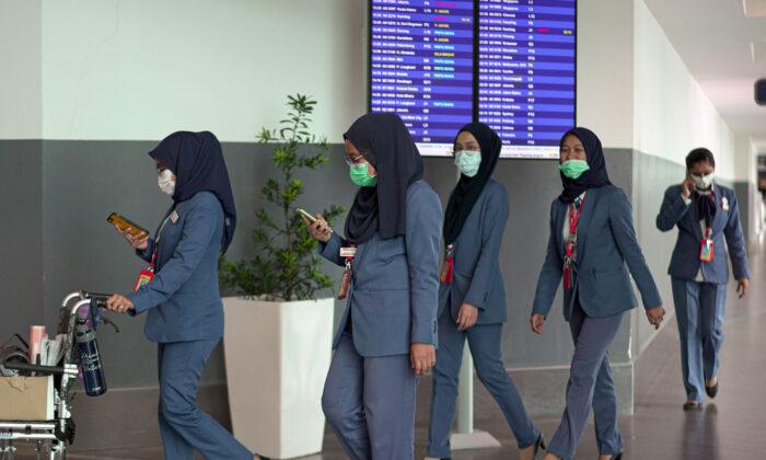 Airport staff wearing masks walk through the Kuala Lumpur International Airport 2 in Malaysia on Feb. 4, 2020. (Ore Huiyang/Getty Images)