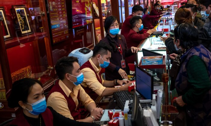 Gold shop employees wear face masks while serving customers in Hanoi, Vietnam, on Feb. 3, 2020. (Linh Pham via Getty Images)