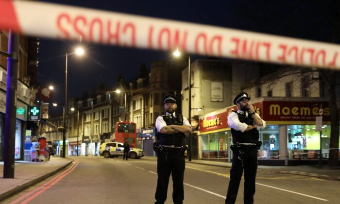 """Police officers in Streatham, South London, after at least two people were stabbed in a suspected """"terrorist-related"""" incident on Feb. 2, 2020. (Isabel Infantes/AFP via Getty Images)"""