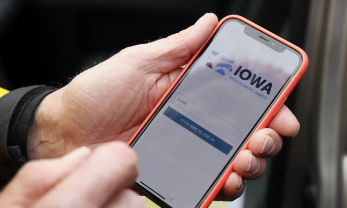 Precinct captain Carl Voss, of Des Moines, Iowa, holds his iPhone that shows the Iowa Democratic Party's caucus reporting app in Des Moines, Iowa, on Feb. 4, 2020. (Charlie Neibergall/AP Photo)