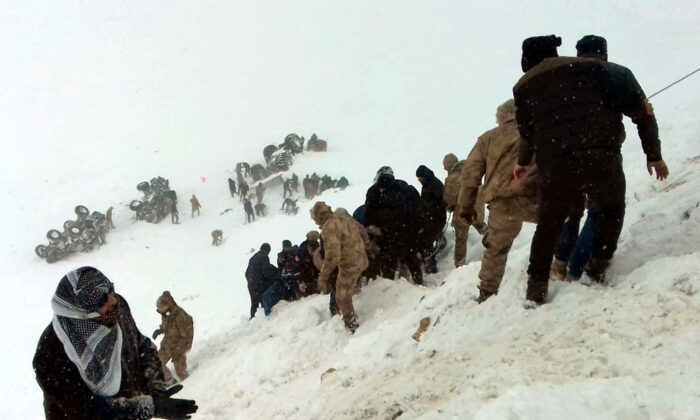 Turkish soldiers and locals try to rescue people trapped under avalanche in Bahcesaray in Van province, Turkey, on Feb. 5, 2020. (Ihlas News Agency (IHA) via Reuters)
