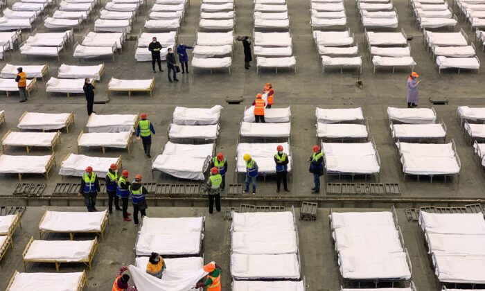 Workers set up beds at a Fangcang hospital in Wuhan, China on Feb. 4, 2020. (STR/AFP via Getty Images)
