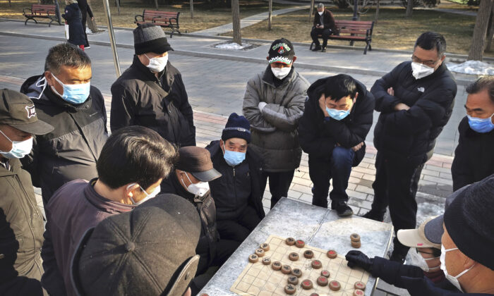 Chinese men all wear protective masks as they play mahjong at a park in Beijing, China on Jan. 31, 2020. (Kevin Frayer/Getty Images)