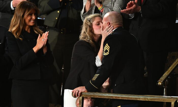 Sgt Townsend Williams, wife, kisses his wife Amy, center, after returning from deployment in Afghanistan as First Lady Melania Trump applauds during the State of the Union address at the US Capitol in Washington on Feb. 4, 2020. (Mandel Ngan/AFP via Getty Images)