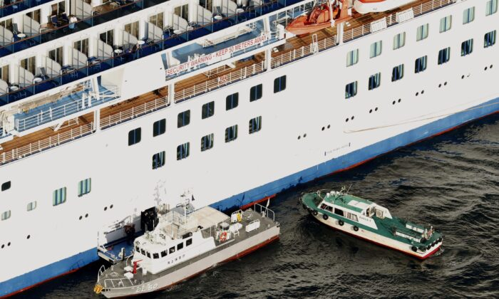 Japan Coast Guard's patrol boat (left) is brought alongside the cruise ship Diamond Princess to take passengers who tested positive for coronavirus to hospitals off Yokohama, south of Tokyo, on Feb. 5, 2020. (Hiroko Harima/Kyodo News via AP)