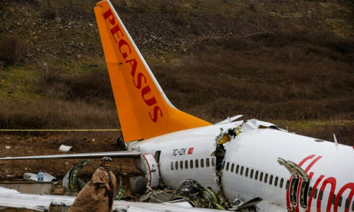 Soldiers guard the wreckage of a plane operated by Pegasus Airlines after it skidded Wednesday off the runway at Istanbul's Sabiha Gokcen Airport, in Istanbul, Turkey, on Feb. 6, 2020.(Emrah Gurel/AP)