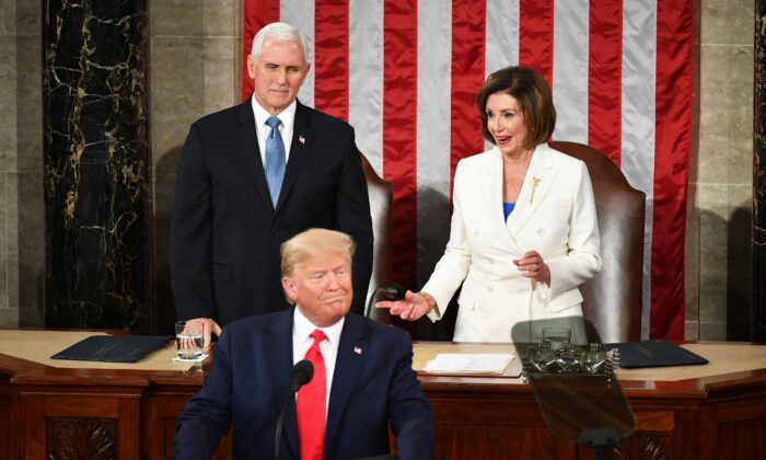 Vice President Mike Pence (L) watches as House Speaker Nancy Pelosi (D-Calif.) reacts after reaching out to shake hands with President Donald Trump as he arrives to deliver the State of the Union address in the House chamber of the U.S. Capitol in Washington, on Feb. 4, 2020. (Mandel Ngan/AFP via Getty Images)