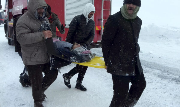 Emergency service members carry a casualty at the site of avalanche near the town of Bahcesehir,