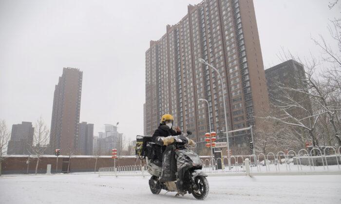 A food delivery worker rides his bike amid snow at a residential compound, as the country is hit by an outbreak of the novel coronavirus, in Beijing, China on Feb. 6, 2020.  (Reuters)
