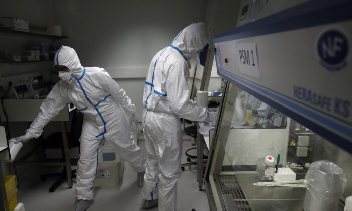 French lab scientists in hazmat gear inserting liquid in test tube manipulate potentially infected patient samples at Pasteur Institute in Paris on Feb. 6, 2020. (Francois Mori/AP Photo)