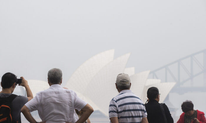 Tourists are seen taking photographs at Mrs Macquarie Point lookout  in Sydney, Australia on Jan. 8, 2020. (Jenny Evans/Getty Images)