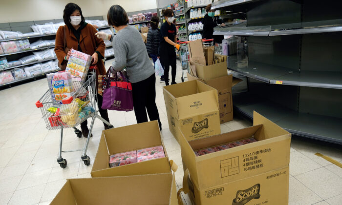 Customers wear masks as they pick facial tissues in a supermarket, following the outbreak of a new coronavirus, in Hong Kong, China on Feb. 7, 2020. (Tyrone Siu/Reuters)