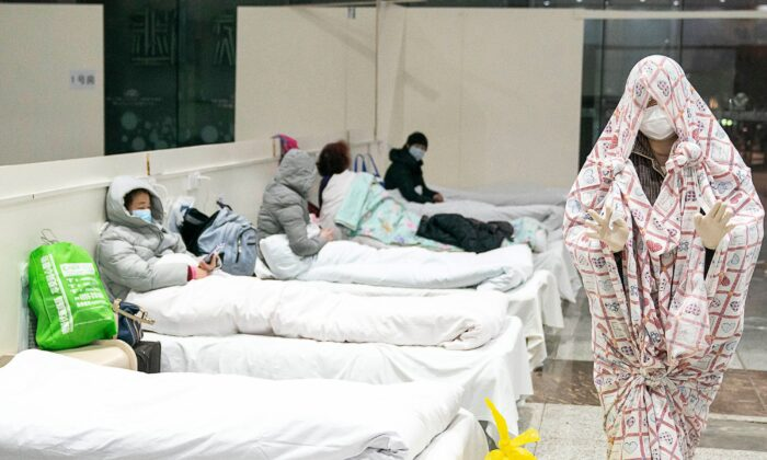 A patient covers with a bed sheet to make him warm at an exhibition centre converted Fangcang Hospital in Wuhan, China on Feb. 5, 2020. (STR/AFP via Getty Images)