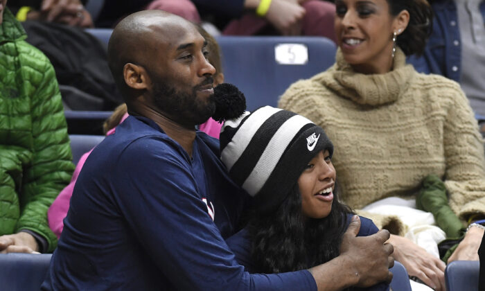 Kobe Bryant and his daughter Gianna watch the first half of an NCAA college basketball game between Connecticut and Houston in Storrs, Conn., on March 2, 2019. (Jessica Hill/AP Photo)