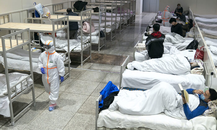 Medical worker in protective suit walks by patients diagnosed with the coronaviruses in a temporary hospital transformed from an exhibition center in Wuhan in central China's Hubei province on Feb. 5, 2020. (Chinatopix via AP)