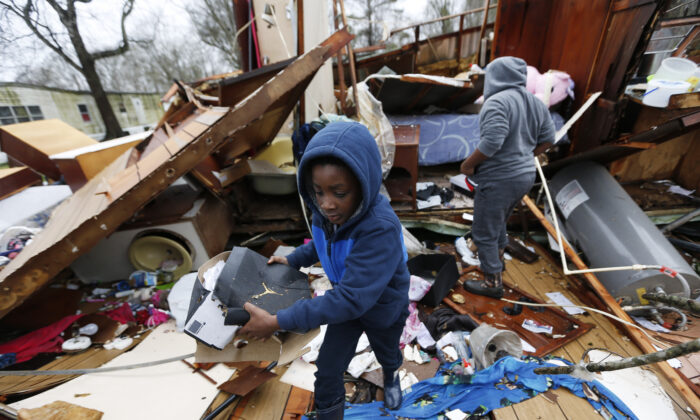 Emma Carter's grandsons comb the remains of her mobile home, looking for salvageable clothing and personal items after severe weather hit the area, in Pickens, Miss., on Feb. 6, 2020. (Rogelio V. Solis/AP)