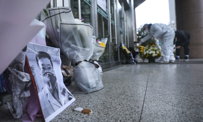 People pay condolence in front of flowers lying near a photo of the late Dr. Li Wenliang at a hospital in Wuhan in central China's Hubei Province, on Feb. 7, 2020. The death of the doctor who was reprimanded for warning about China's new virus triggered an outpouring on Friday of praise for him and fury that communist authorities put politics above public safety. In death. (Chinatopix via AP)