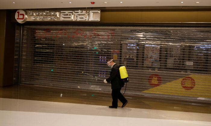A staff member carrying sanitizing equipment walks past a closed cinema at a shopping mall, as the country is hit by the outbreak of the new coronavirus, in Beijing, China on Feb. 3, 2020. (Carlos Garcia Rawlins/Reuters)