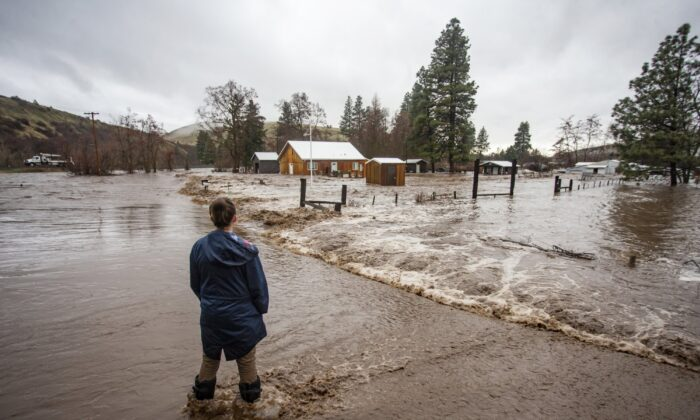 Chantel Fuller watches as water floods her home in Thorn Hollow outside of Adams, Ore., on Feb. 6, 2020. (Ben Lonergan/East Oregonian via AP)