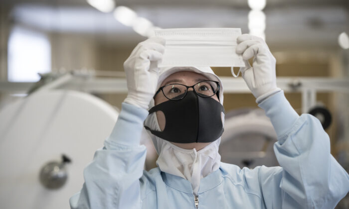 An employee inspects a disposable face mask on the production line of the Yokoi Co. Ltd. factory in Nagoya, Japan on Feb. 06, 2020. (Tomohiro Ohsumi/Getty Images)
