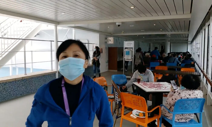 Passengers wear protective masks aboard the World Dream cruise ship, being quarantined at Kai Tak Cruise Terminal amid concerns of coronavirus infections, in Hong Kong, China on Feb. 8, 2020 in this still image obtained from social media video. (Dr. Peter Lo via Reuters)