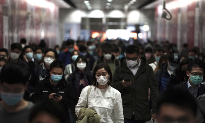 People wearing masks, walk in a subway station in Hong Kong on Feb. 7, 2020. (AP Photo/Kin Cheung)