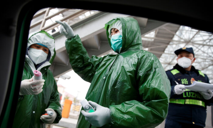 Medical workers and security personell stand at a checkpoint as the country is hit by an outbreak of the novel coronavirus in Anqing, Anhui province, China, on Feb. 6, 2020. (Thomas Peter/Reuters)