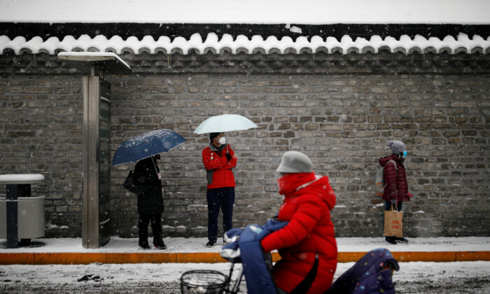 People wearing masks wait amid snow at a bus stop as the country is hit by an outbreak of the novel coronavirus, in Beijing, China on Feb. 6, 2020. (Carlos Garcia Rawlins/Reuters)