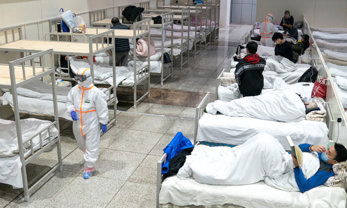 Medical workers in protective suits attend to patients at the Wuhan International Conference and Exhibition Center, which has been converted into a makeshift hospital to receive patients with mild symptoms caused by the novel coronavirus, in Wuhan, Hubei Province, China on Feb. 5, 2020. (China Daily via Reuters)