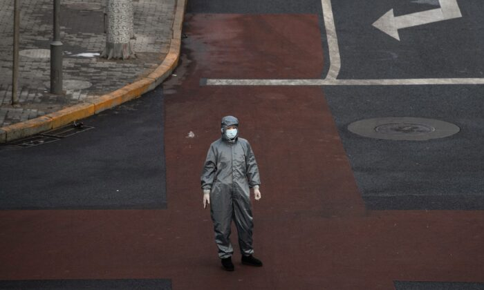 A Chinese woman wears a protective suit and mask as she waits to cross the intersection of a nearly empty street in Beijing, China on Feb. 8, 2020. (Kevin Frayer/Getty Images)