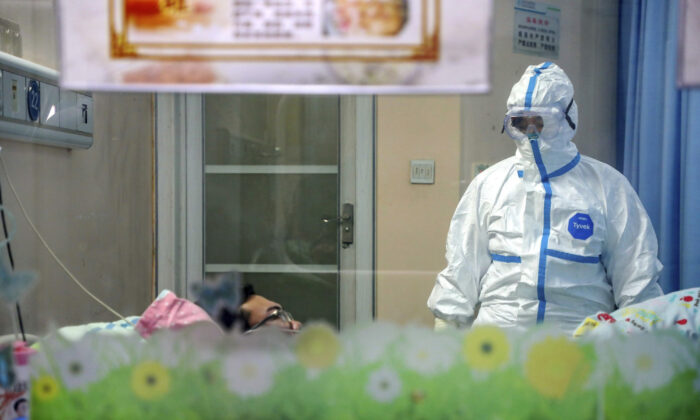 A doctor attends to a patient in an isolation ward at a hospital in Wuhan in central China's Hubei Province, on Jan. 30, 2020. (Chinatopix via AP)