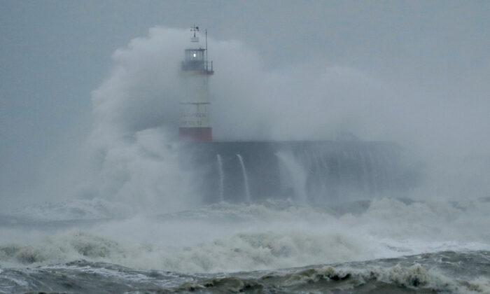Waves crash over the harbor and a lighthouse, as Storm Ciara hits Newhaven, on the south coast of England, on Sunday, Feb. 9, 2020. (Matt Dunham/AP Photo)