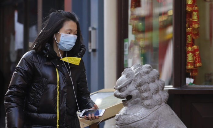 A woman wears a mask as she walks through China Town in London, on Feb. 7, 2020. (Kirsty Wigglesworth/AP photo)