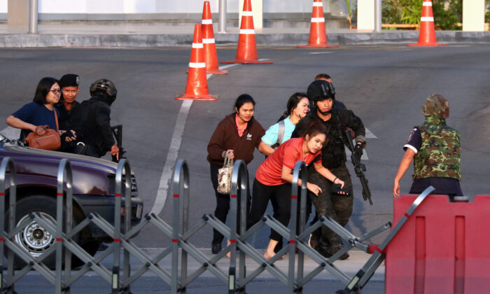 Thai security forces evacuate people who were stranded inside the Terminal 21 shopping mall following a gun battle, to try to stop a soldier on a rampage after a mass shooting, Nakhon Ratchasima, Thailand, on Feb. 9, 2020. (Athit Perawongmetha/Reuters