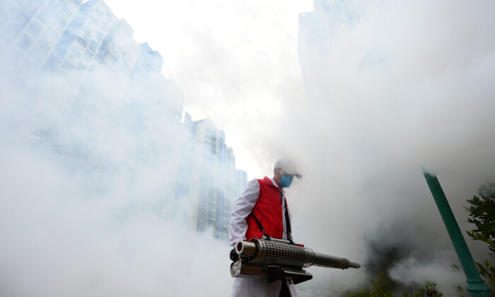A volunteer disinfects a residential compound to prevent and control the novel coronavirus, in Ganzhou, Jiangxi Province, China, on Feb. 6, 2020. (China Daily via Reuters)