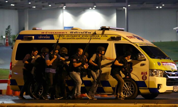 Thailand security forces take cover behind an ambulance as they chase a shooter hidden in a shopping mall after a mass shooting in front of the Terminal 21, in Nakhon Ratchasima, Thailand, on Feb. 9, 2020. (Athit Perawongmetha/Reuters)