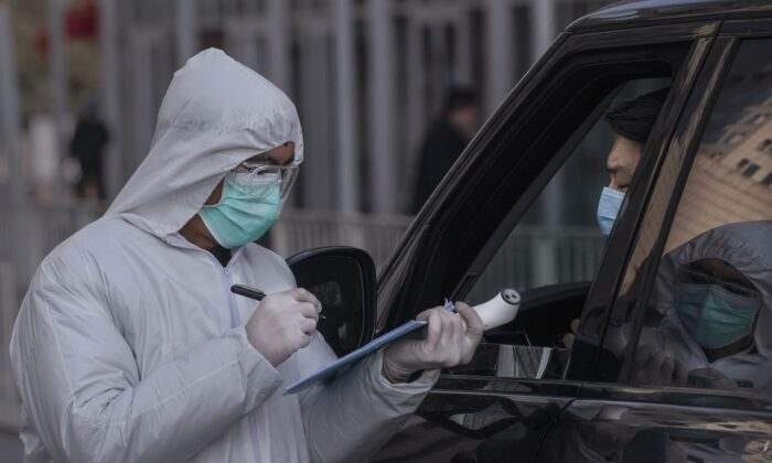 A Chinese worker wears a protective suit as he takes the name of a driver in a vehicle entering an office building while checking people in Beijing on Feb. 10, 2020. (Kevin Frayer/Getty Images)