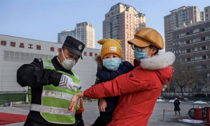 A Chinese woman wears a protective mask as she has her temperature checked before entering a park with her child in Beijing, China, on Feb. 9, 2020. (Kevin Frayer/Getty Images)
