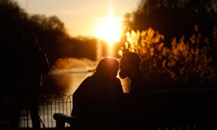 A couple kiss as the sun sets in St. James's Park on Valentine's Day on Feb. 14, 2019. (Tolga Akmen/AFP via Getty Images)