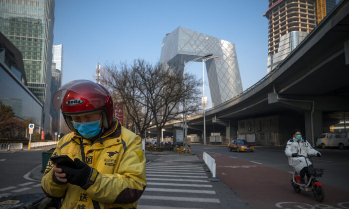 A delivery man uses his phone in the streets of the Central Business District in Beijing, China on Feb. 10, 2020. (Andrea Verdelli/Getty Images)