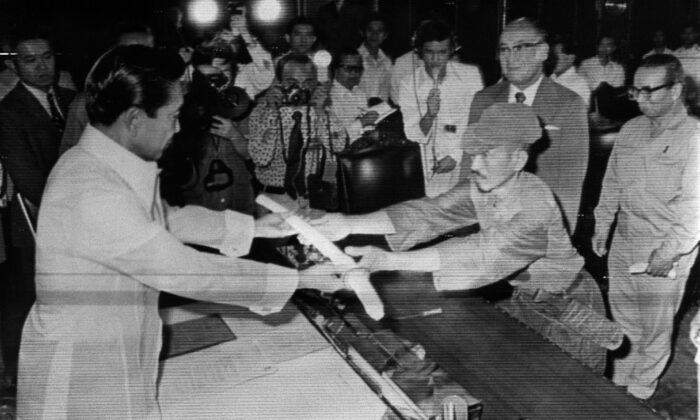 Former Japanese imperial army soldier Hiroo Onoda (R) offers his military sword to former Philippine President Ferdinand Marcos (L) to express his surrender at the Malacanan Palace in Manila on March 11, 1974. Onoda, who hid in the Philippine jungle for three decades because he did not believe World War II was over, died in Tokyo on Jan. 17, 2014, at the age of 91. The former soldier waged a guerrilla campaign in Lubang Island near Luzon until he was finally persuaded in 1974 that peace had broken out. (JiJi Press/AFP via Getty Images)